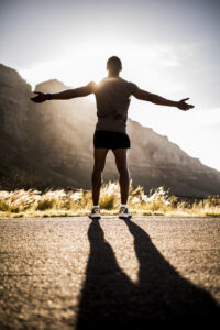 Rear view of a male athlete with his arms outstretched, looking out over a mountain